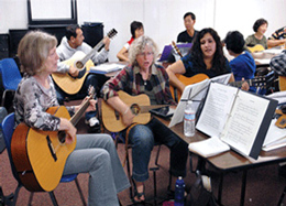 Group of adult guitar students playing instruments