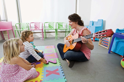 Woman playing the guitar to young children