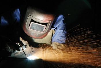 Person wearing protective helmet welding with torch